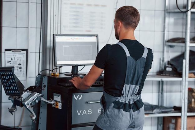 L'uomo in officina in uniforme usa il computer per il suo lavoro per riparare la macchina rotta