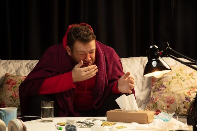 L'uomo avvolto in un plaid sembra malato, malato, starnutisce e tossisce seduto a casa in casa