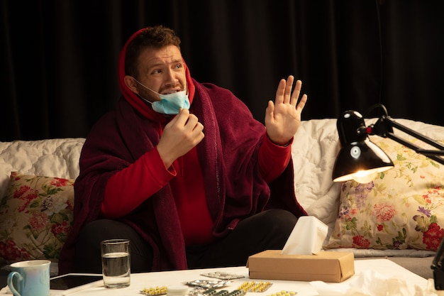 L'uomo avvolto in un plaid che indossa una maschera facciale che cerca di proteggersi dai malati di qualcuno, sembra disilluso, arrabbiato, triste seduto sul divano di casa al chiuso. sanità e medicina, prevenzione delle malattie.