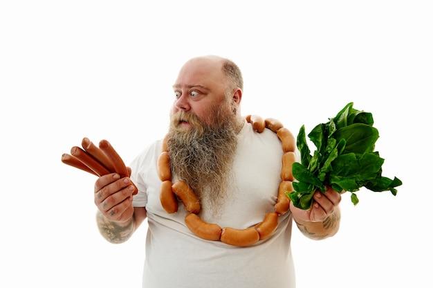 Un uomo avvolto in salsicce che guarda avidamente le salsicce nella sua mano e nell'altra tiene gli spinaci nell'altra