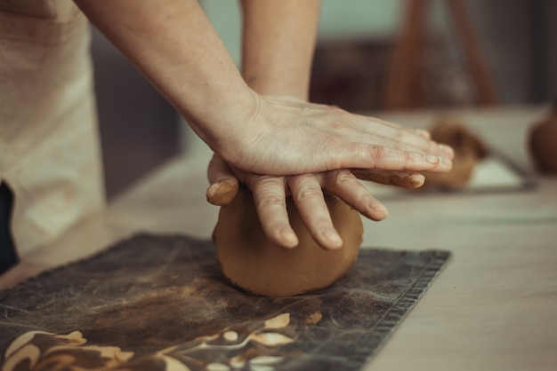 Un uomo raggrinzisce l'argilla con le mani