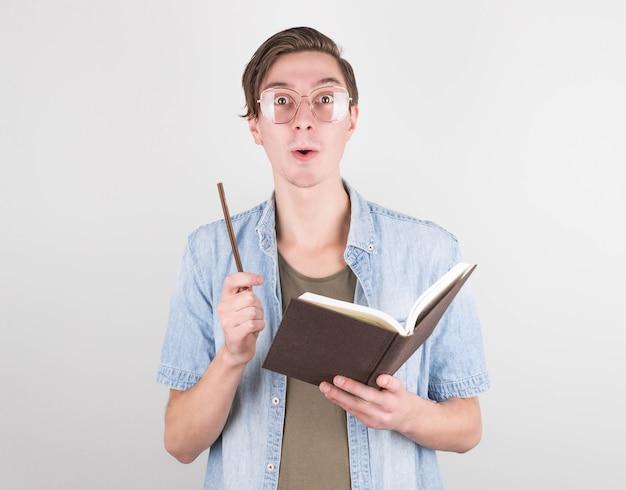 Uno scrittore con i capelli scuri e gli occhiali ha escogitato cosa scrivere in un libro, lo mostra con una matita in mano, tiene un libro nell'altra. giornata internazionale degli scrittori