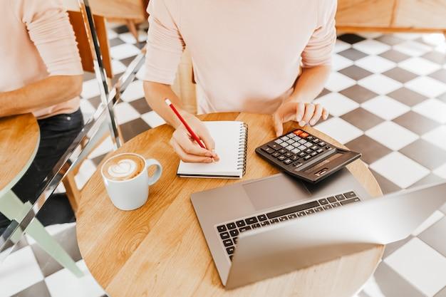 L'uomo scrive informazioni aziendali in notebook sul posto di lavoro in ufficio con calcolatrice e laptop
