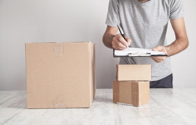 Uomo che scrive negli appunti. scatole di cartone sulla scrivania. prodotti, commercio, vendita al dettaglio, consegna