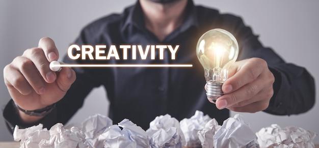 Uomo che scrive la parola creatività sullo schermo e tenendo la lampadina.