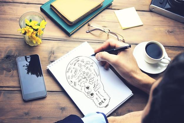 Uomo che scrive su carta idea su tavolo da lavoro in legno