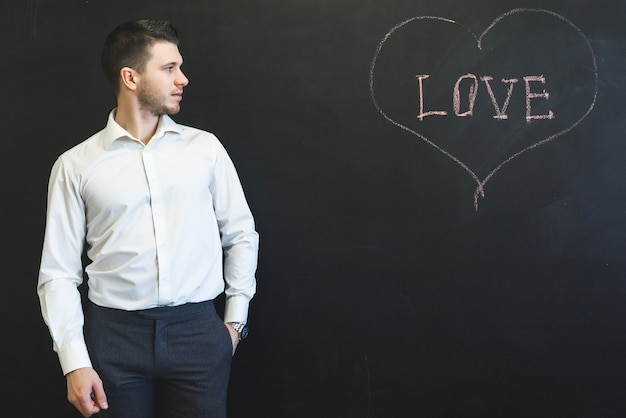 L'uomo ha scritto la parola amore sulla lavagna e cerca di copyspace