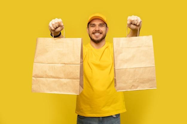 Uomo in berretto giallo, maglietta che dà i pacchetti di carta vuoti isolati. corriere dipendente maschio tenere pacchetti di carta con il cibo