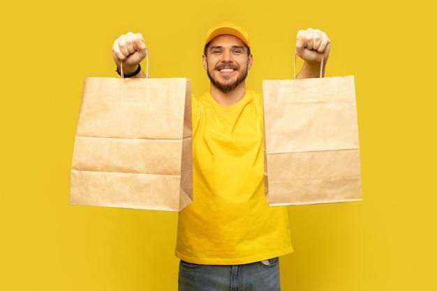Uomo in berretto giallo, maglietta che dà i pacchetti di carta isolati. corriere dipendente maschio tenere pacchetti di carta con il cibo