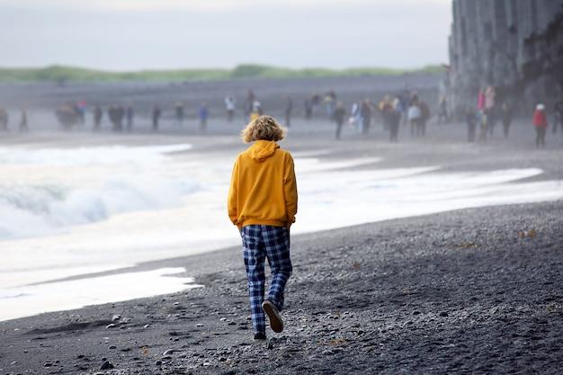 Un uomo con una giacca gialla è sulla sabbia nera della spiaggia d'islanda. unità con la natura e riposo in un viaggio