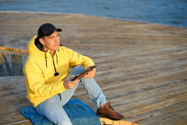 Uomo in un impermeabile giallo e un berretto nero seduto sul molo con un tablet guardando l'alba