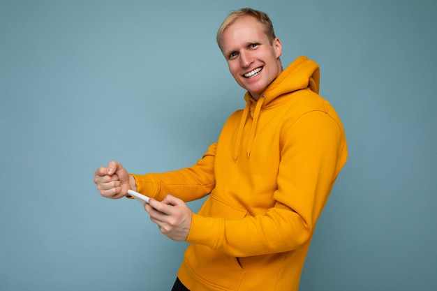 Un uomo con una felpa gialla con un telefono cellulare.