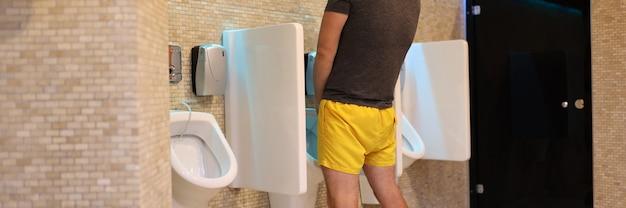 Uomo in lana gialla che fa pipì nel ritratto del bagno pubblico
