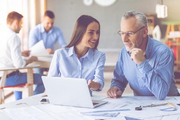 L'uomo e la giovane donna d'affari stanno usando un computer portatile e sorridente