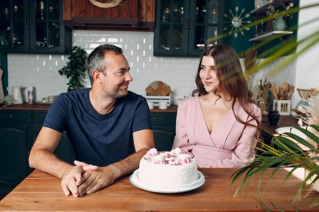 L'uomo e la giovane donna si siedono nella cucina di casa con la torta sul tavolo.
