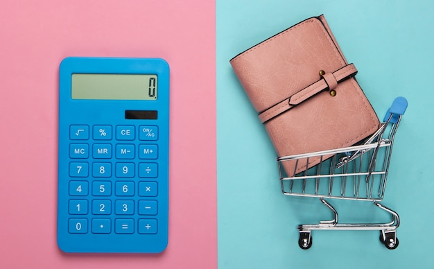 Gestisci il budget familiare. costi di acquisto. calcolatrice blu, portafoglio in pelle, carrello della spesa su pastello blu rosa