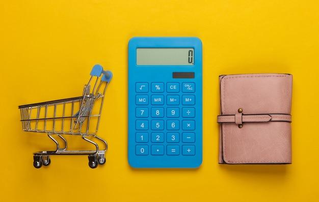 Gestisci il budget familiare. costi di acquisto. calcolatrice blu, portafoglio in pelle, carrello della spesa su giallo