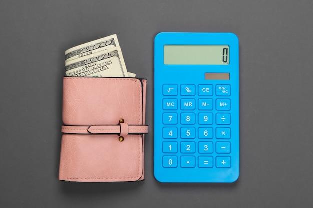 Gestisci il budget familiare. costi di acquisto. calcolatrice blu e portafoglio in pelle con banconote da un dollaro su grigio