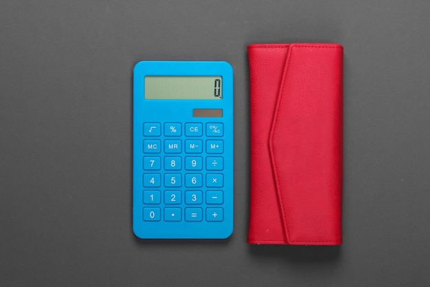 Gestisci il budget familiare. costi di acquisto. calcolatrice blu con portafoglio in pelle rossa su grigio