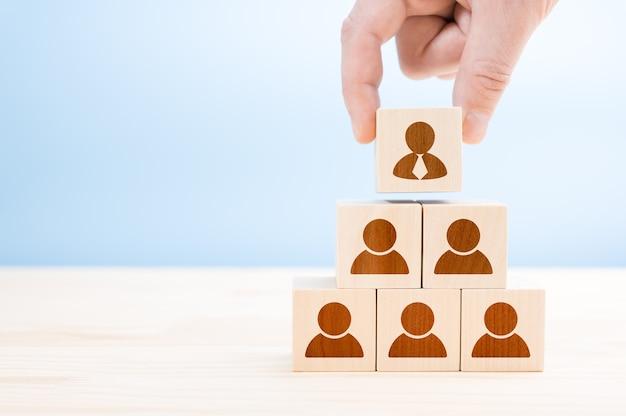 Piramide della gerarchia di gestione con cubi di legno sull'azzurro. risorse umane, concetto di gerarchia aziendale