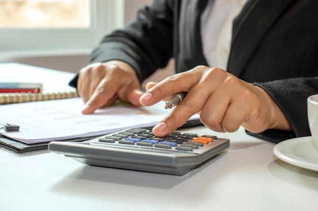 Idee di gestione per contabilità, finanza e manager che calcolano il proprio reddito con una calcolatrice.
