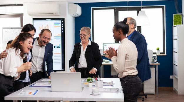 Il team di gestione che applaude felicissimo nella sala conferenze dopo un buon allenamento. i colleghi dei partner multietnici celebrano il successo del lavoro di squadra durante il briefing aziendale