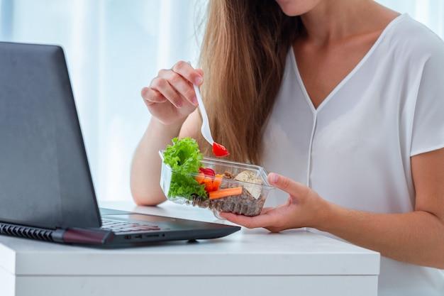 Manager mangiare pasti da asporto pranzo al posto di lavoro durante la pausa pranzo. contenitore per alimenti al lavoro