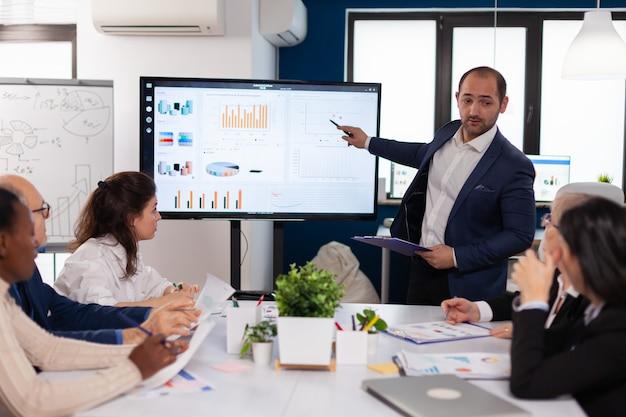 Manager che tiene la presentazione del briefing nel progetto del monitor della sala conferenze. personale aziendale che discute di una nuova applicazione aziendale con i colleghi che guardano lo schermo