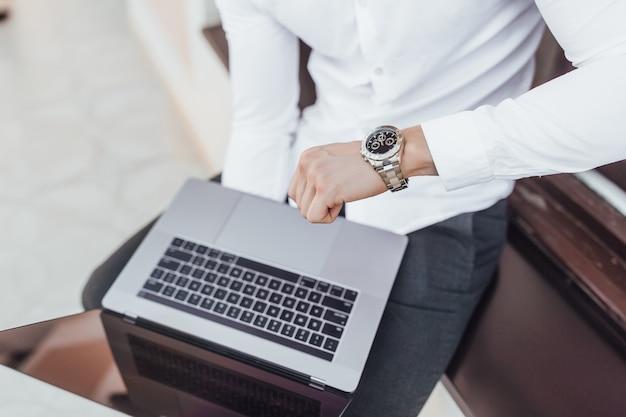 Il manager tiene un laptop e guarda l'orologio