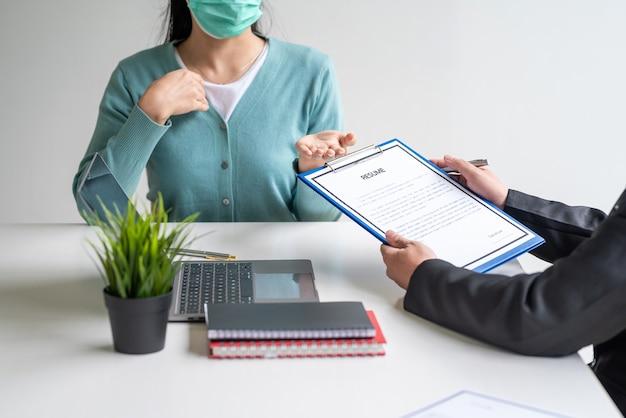 Colloquio di lavoro del manager con curriculum indossare una maschera per prevenire i germi in ufficio.