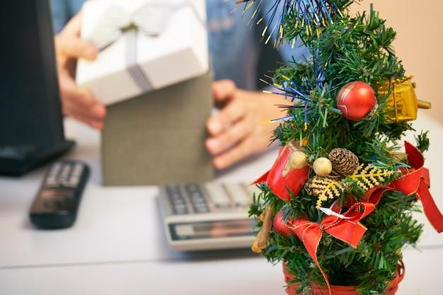 Manager che apre una confezione regalo sul posto di lavoro nella vigilia di capodanno