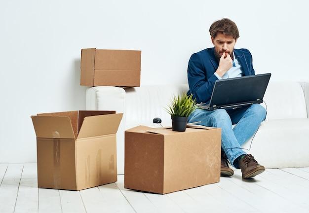 Il manager si siede sul divano con un laptop che lavora scatole professionali con le cose