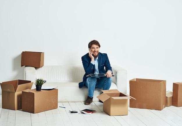 Il manager si siede su un divano bianco con le cose che si muovono professionalmente