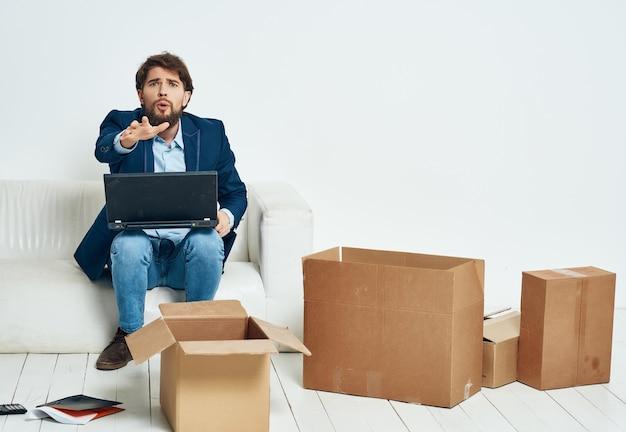 Manager seduto sul divano con un laptop che si muove disimballando le cose in ufficio