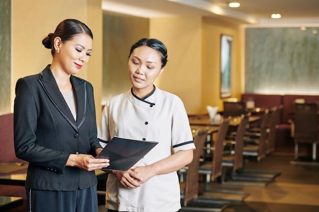 Manager e cameriera che leggono un menu