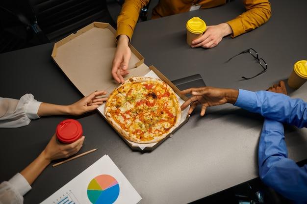 I manager mangiano la pizza, pranzo di lavoro nell'ufficio it