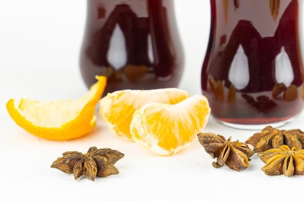 Pezzi di mandarino con semi di anice davanti a bicchieri con vino rosso