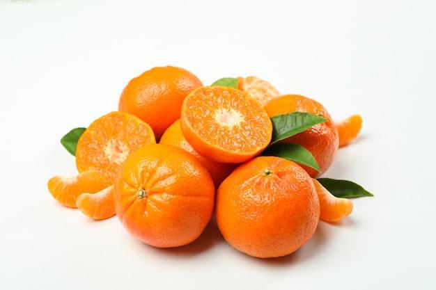 Mucchio di mandarino con foglie su sfondo bianco