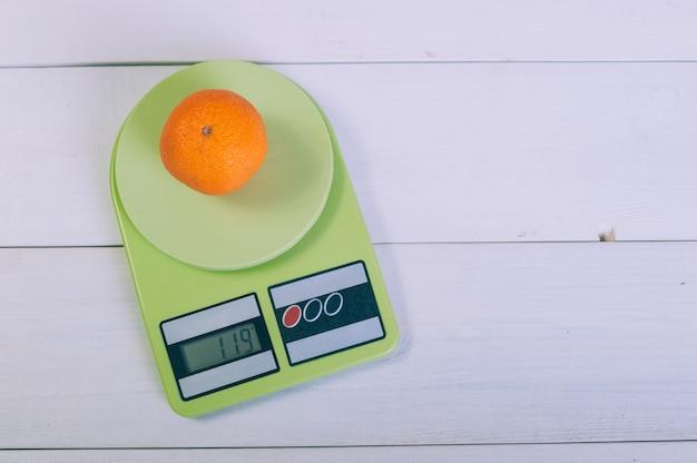 Mandarino sulle scale su un tavolo di legno.