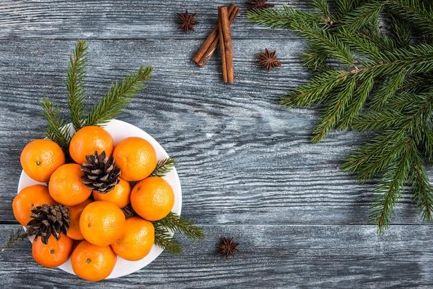 Mandarini su legno con rami di abete di natale, bastoncini di cannella, stelle di anice e coni.