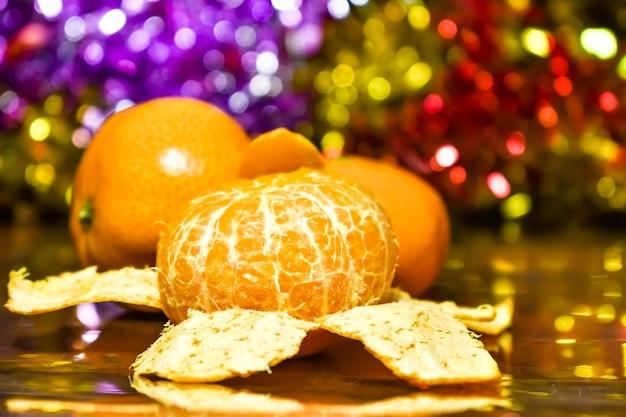Mandarini su uno sfondo di luci multicolori sfocate sfocate e tinsel.