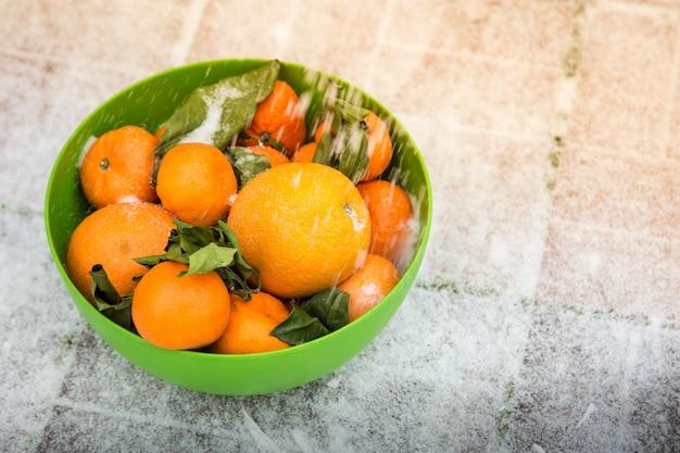 Mandarini e arance nella ciotola verde sulla neve sta sulla strada foglie verdi appassite da