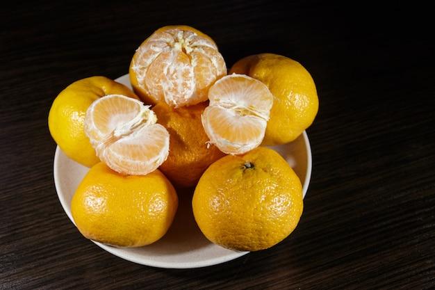 Mandarini in un piatto sul tavolo di legno scuro
