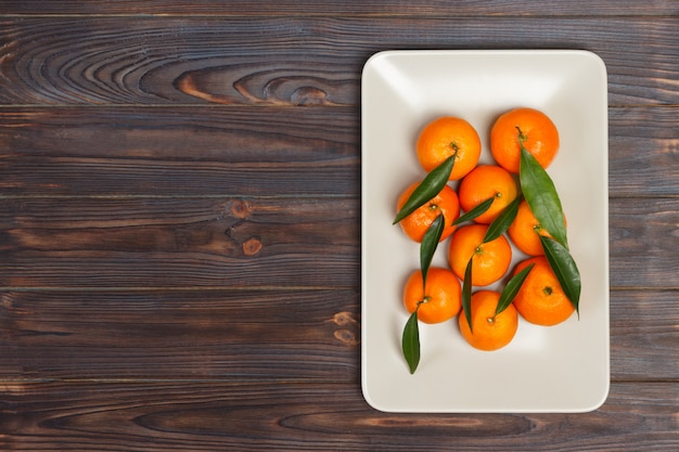 Mandarini su un piatto natura morta con mandarini sul tavolo di legno