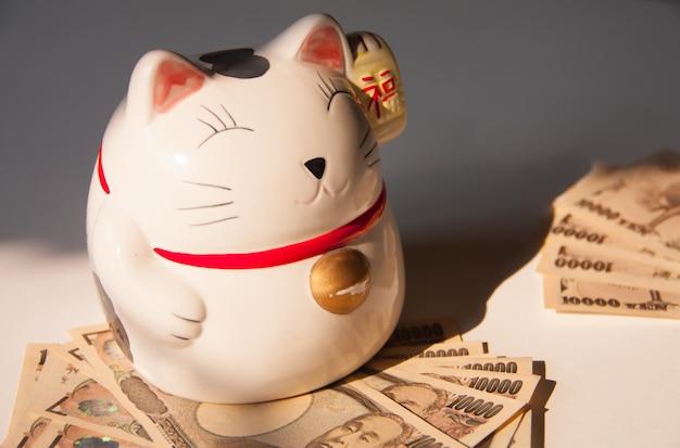 Maneki-neko, gatto giapponese fortunato con banconota yen