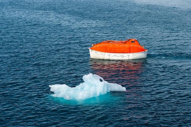 Manovra di salvataggio arancione in acqua nelle acque artiche, svalbard. abbandonare il trapano per nave. addestramento della scialuppa di salvataggio. trapano uomo a mare.
