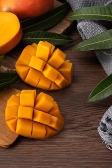 Mango. primo piano di frutta fresca di mango maturo con foglie su sfondo tavolo in legno scuro con foglie verdi.