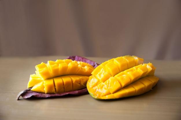 Mango tagliato a fette su una foglia su fondo beige