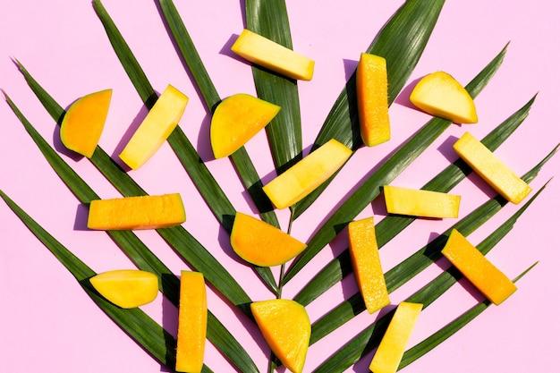Pezzi tagliati di mango su foglie di palma su sfondo rosa. vista dall'alto