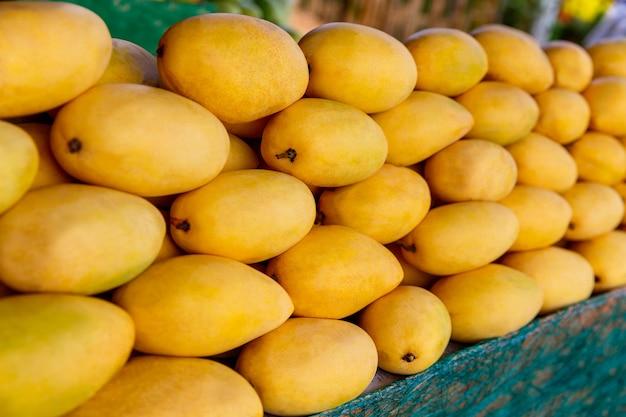 Stand del festival del mango con frutti di mango gialli freschi nel fuoco selettivo del mercato di strada
